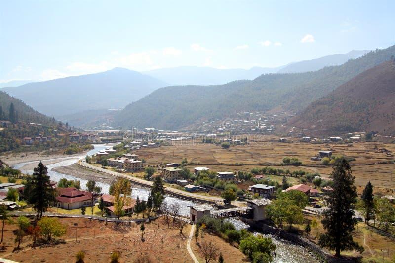 Ponte attraverso il fiume con le case tradizionali di stile del Bhutanese immagini stock
