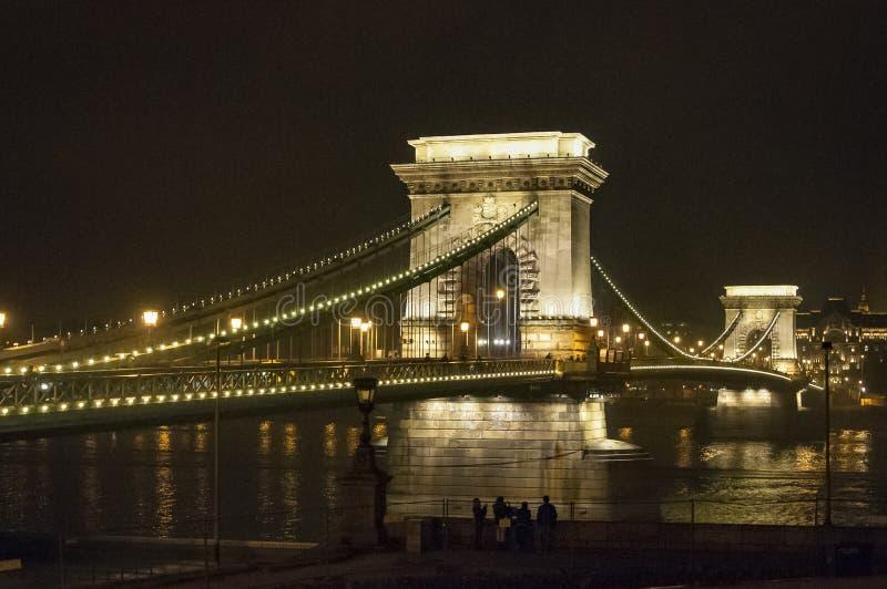 A ponte Chain de Budapest é iluminada na noite com vista de Danube River fotografia de stock