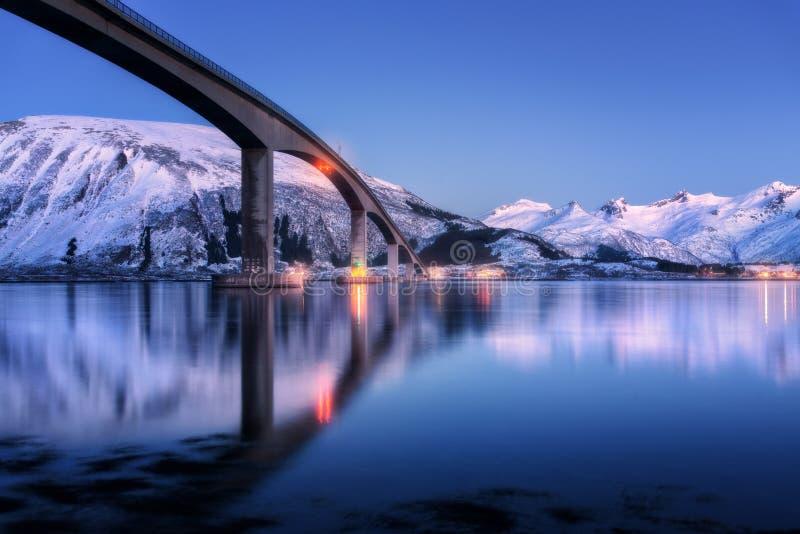 Ponte com iluminação, montanhas cobertos de neve, céu azul fotografia de stock royalty free