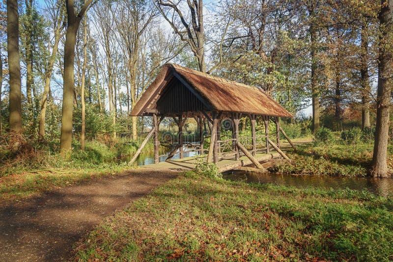 A ponte com o telhado colocou sobre um canal no parque fotografia de stock royalty free