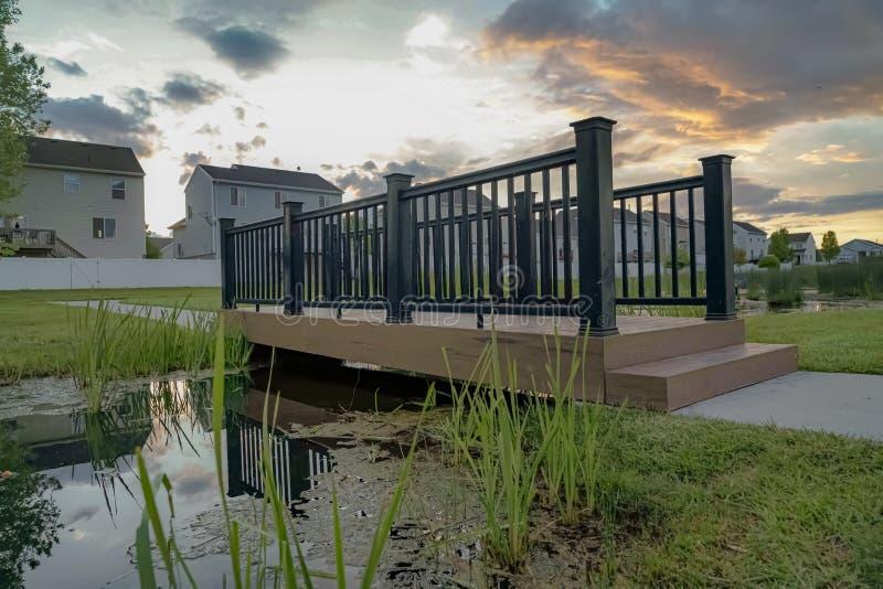 Ponte con la piattaforma di legno e guardavia nera sopra un piccolo e stagno brillante immagini stock