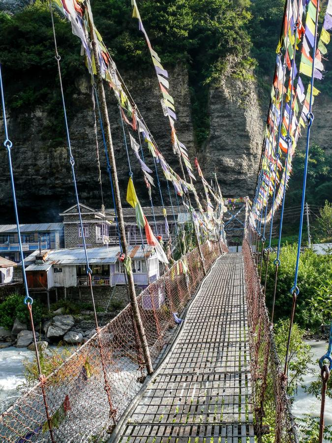 Ponte con le bandiere di preghiera sopra il fiume Chame, Nepal di Marsyangdi fotografie stock libere da diritti