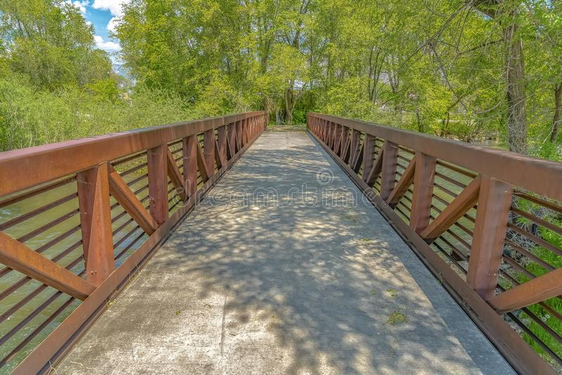 Ponte con le guardavie arrugginite del metallo sopra un lago osservato un giorno soleggiato immagine stock libera da diritti