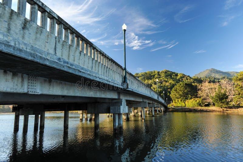 Ponte concreto con il palo leggero sopra il fiume fotografie stock