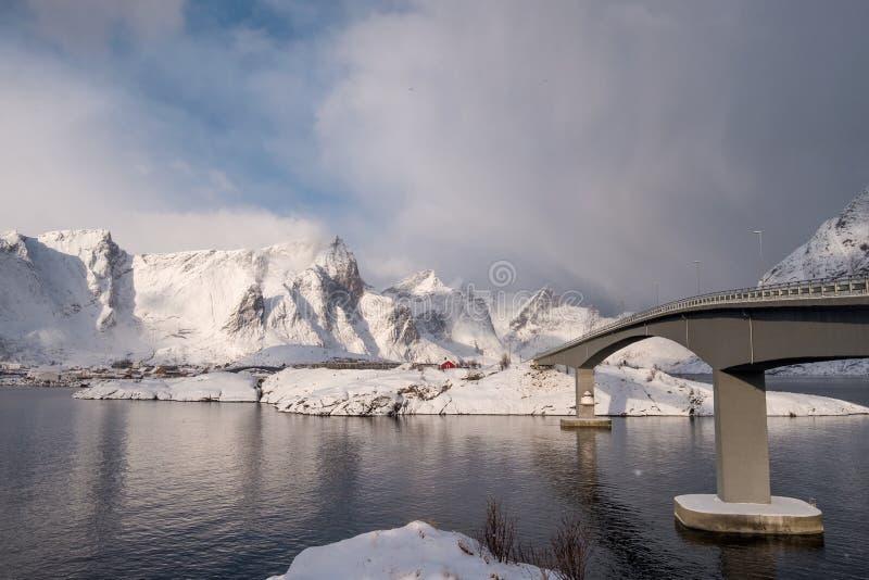 A ponte cruza sobre o oceano ártico com luz solar na montanha foto de stock