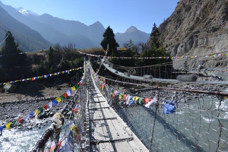 A ponte cruza sobre o rio com fileira da bandeira da oração foto de stock royalty free