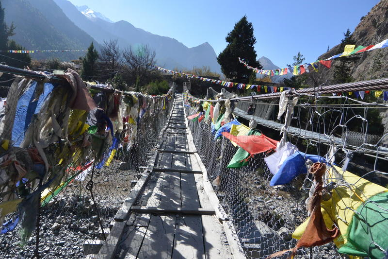 A ponte cruza sobre o rio com fileira da bandeira da oração fotos de stock royalty free