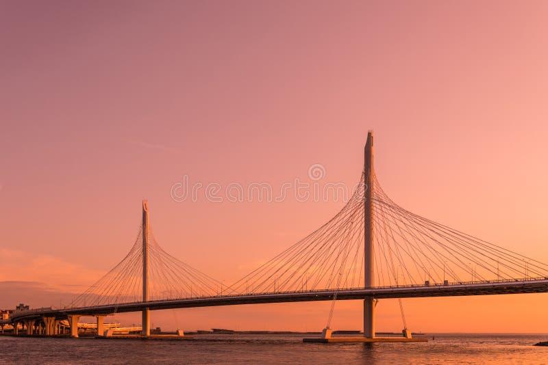 A ponte da estrada da estrada do círculo sobre o rio de Neva perto da boca dela na hora do ouro durante o por do sol imagens de stock royalty free