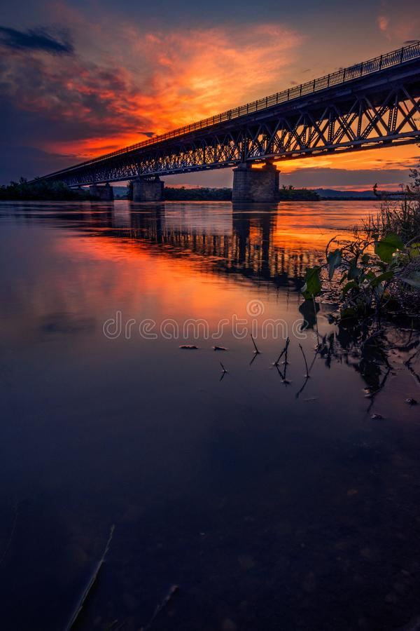 Ponte da estrada que cruza um rio no por do sol com nuvens bonitas sobre imagem de stock royalty free
