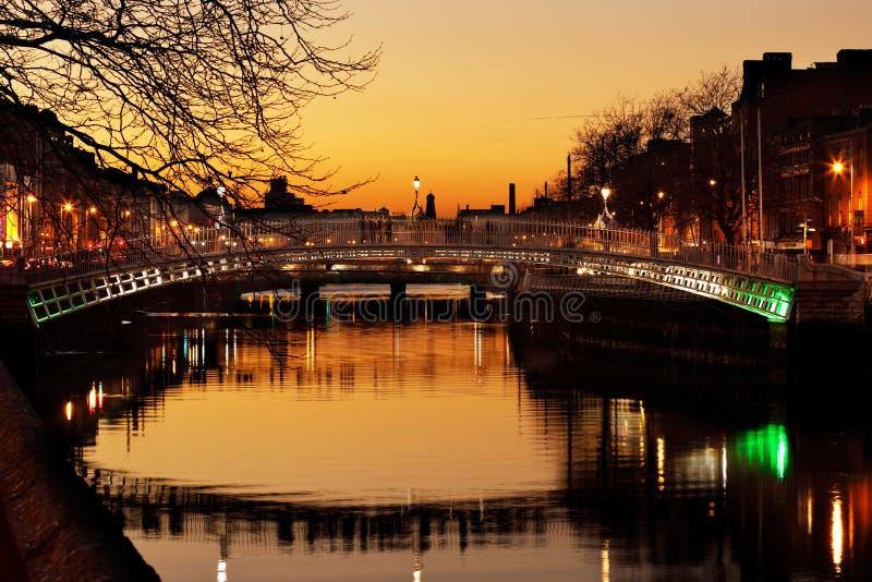 Ponte da moeda de um centavo do ` do Ha e os bancos nortes do rio Liffey em Dublin City Centre na noite fotografia de stock