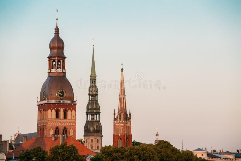A ponte da saia Feche três torres da catedral, do St Peter & do x27 de Riga; igreja de s imagens de stock