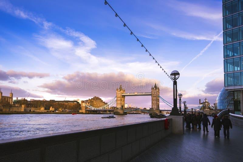 A ponte da torre em Londres na luz morna do por do sol Povos que dão uma volta na passagem imagens de stock royalty free