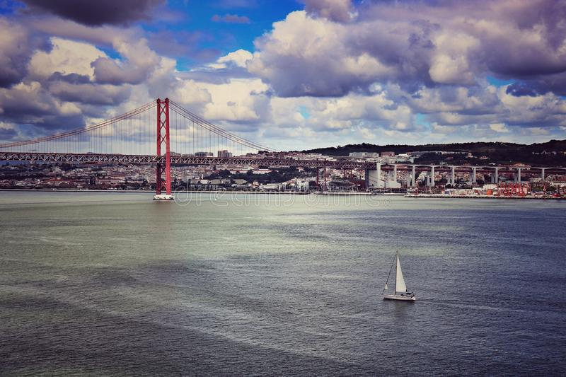Ponte 25 de Abril in Lisbon. A view of Ponte 25 de Abril in Lisbon with a sailing boat on the sea and the city in the background stock photos