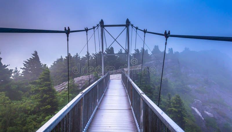A ponte de balanço Milha-alta na névoa, na montanha de primeira geração, N fotografia de stock royalty free