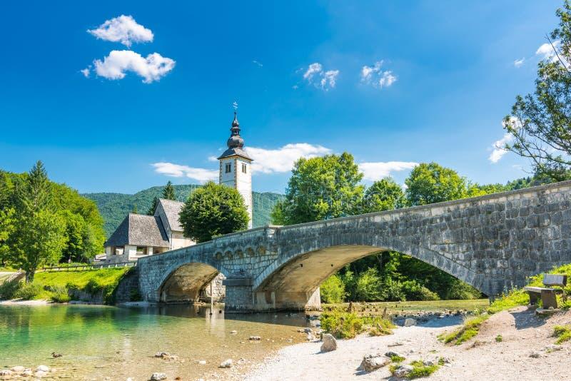 Ponte de Bohinj e igreja, Eslovênia Olhe à ponte antiga histórica velha e à igreja perto do lago Bohinj, em Triglav p nacional foto de stock