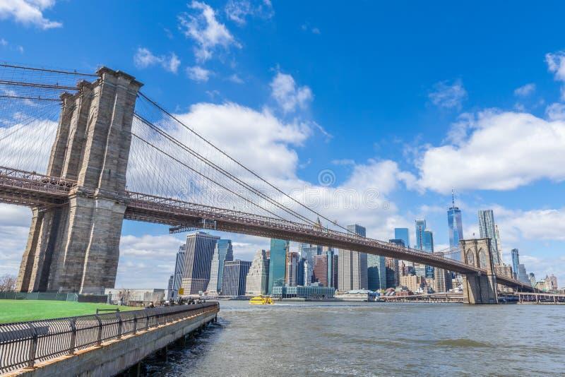 Ponte de Brooklyn com baixa e arquitetura da cidade de Manhattan no dia ensolarado com o céu azul claro New York EUA fotos de stock royalty free