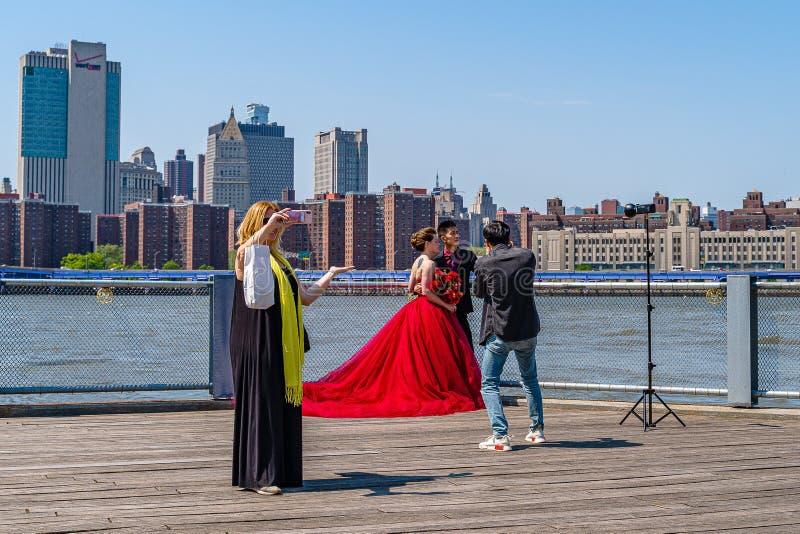 Ponte de Brooklyn com mais baixa skyline de Manhattan, sessão da forma com um vestido vermelho enorme em New York City imagens de stock royalty free