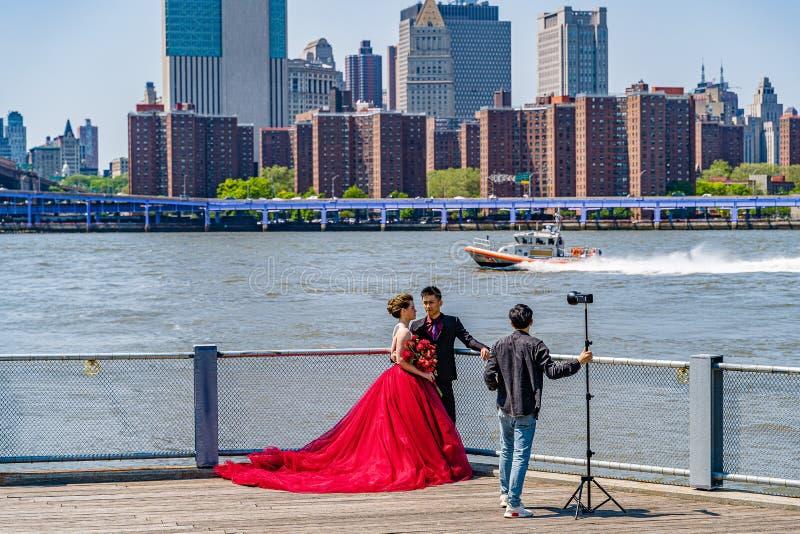 Ponte de Brooklyn com mais baixa skyline de Manhattan, sessão da forma com um vestido vermelho enorme em New York City imagens de stock