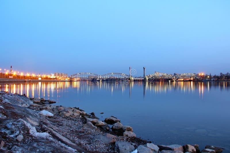 Ponte de estrada de ferro iluminada sobre o rio Neva no por do sol fotos de stock royalty free
