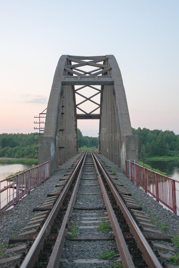 Ponte de estrada de ferro de pedra com os arcos sobre os trilhos e o rio no por do sol no verão imagens de stock royalty free