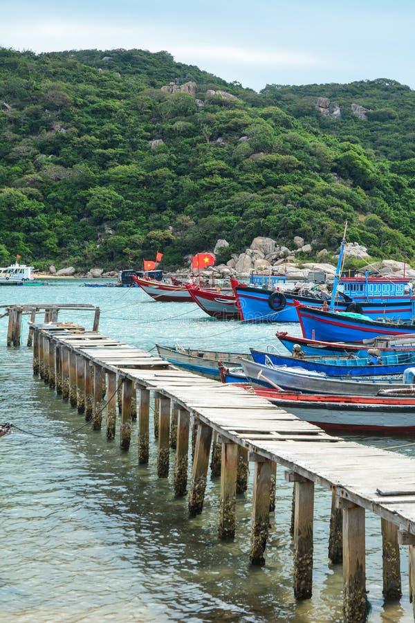 A ponte de madeira com os barcos de pesca em Phan soou, Vietname imagens de stock
