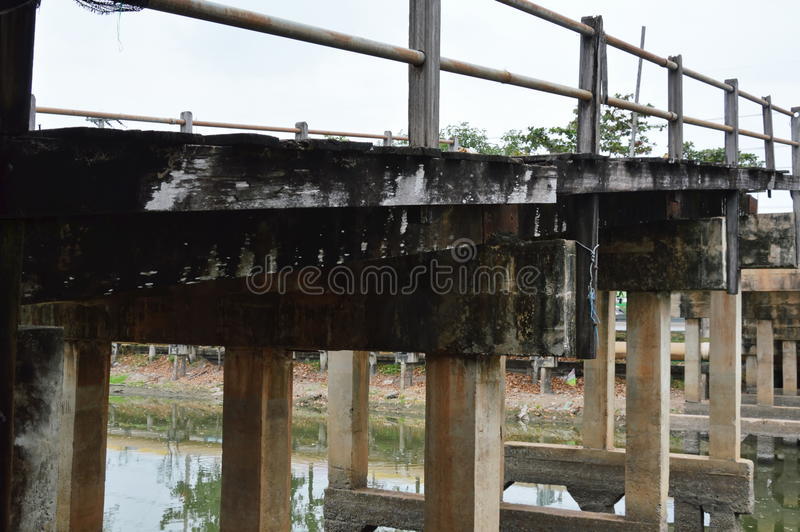Ponte de madeira de dano velho fora de serviço através do canal imagem de stock