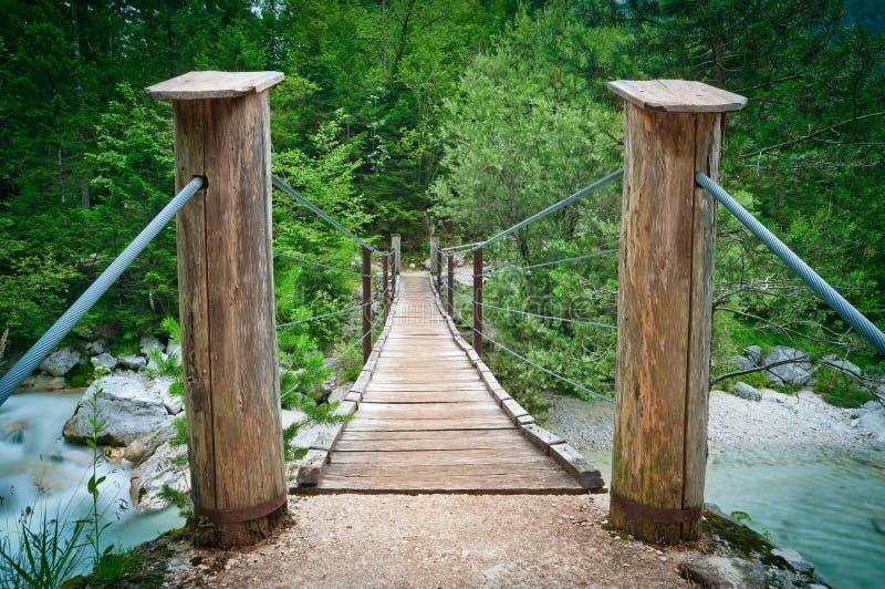 Ponte de madeira de suspensão sobre o rio da montanha fotos de stock royalty free
