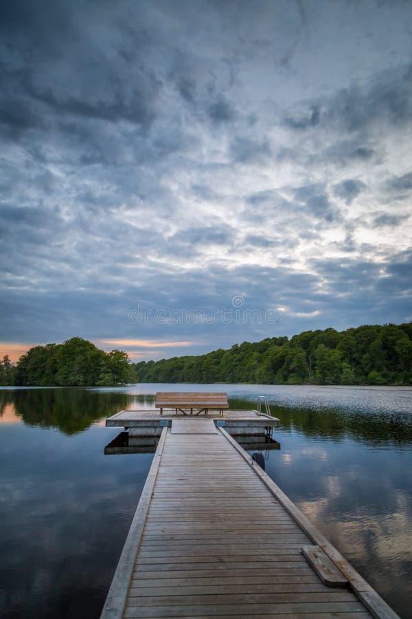 Ponte de madeira do pé que conduz para fora a uma plataforma com um banco em um lago calmo na Suécia foto de stock royalty free