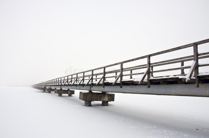 Ponte de madeira longa velha no gelo nevado e na névoa do lago do inverno fotografia de stock royalty free
