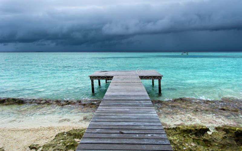 A ponte de madeira na praia estendeu no mar fotos de stock
