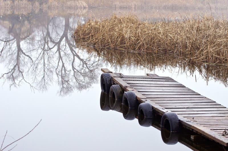 Ponte de madeira no lago do tempo do outono fotos de stock royalty free
