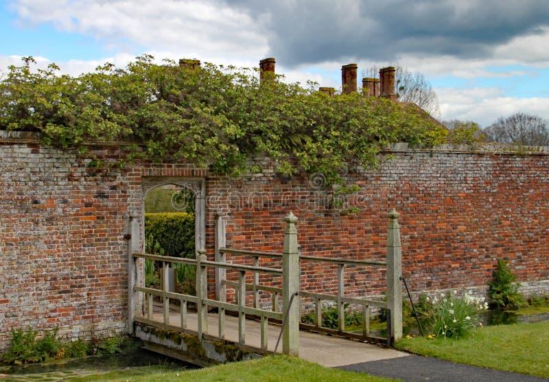 A ponte de madeira pequena com um teste padrão aberto interessante cruza um córrego e condu-lo em um jardim murado fotos de stock royalty free