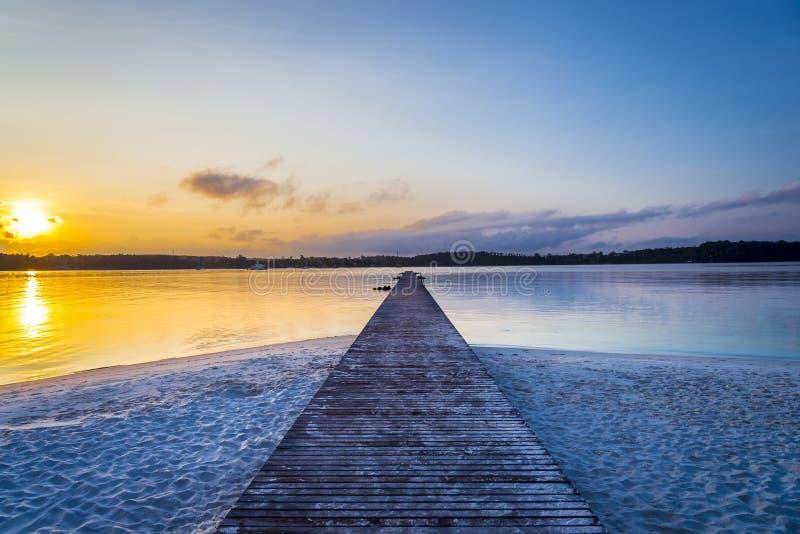 A ponte de madeira por muito tempo ao mar com fundo crepuscular do céu na ilha de KohKham foto de stock