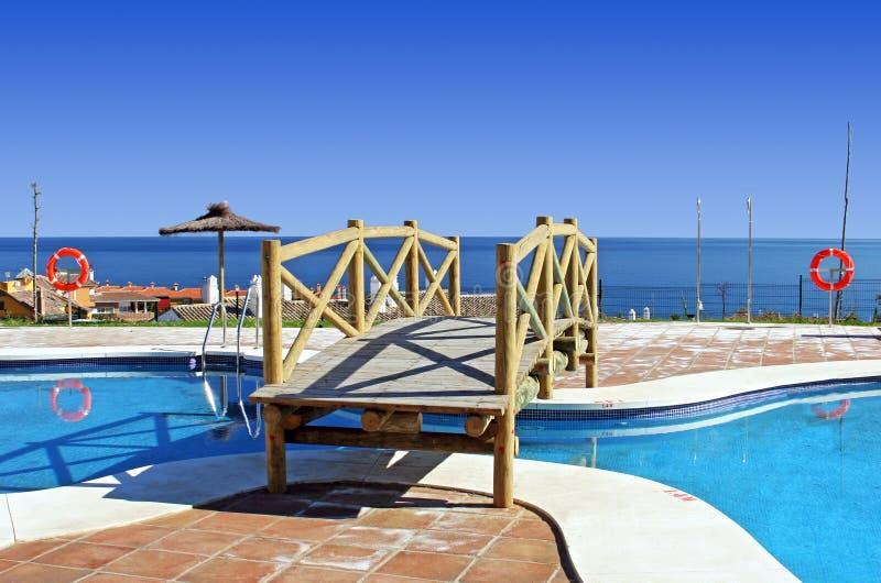 Ponte de madeira sobre a piscina no urbanisation espanhol fotos de stock