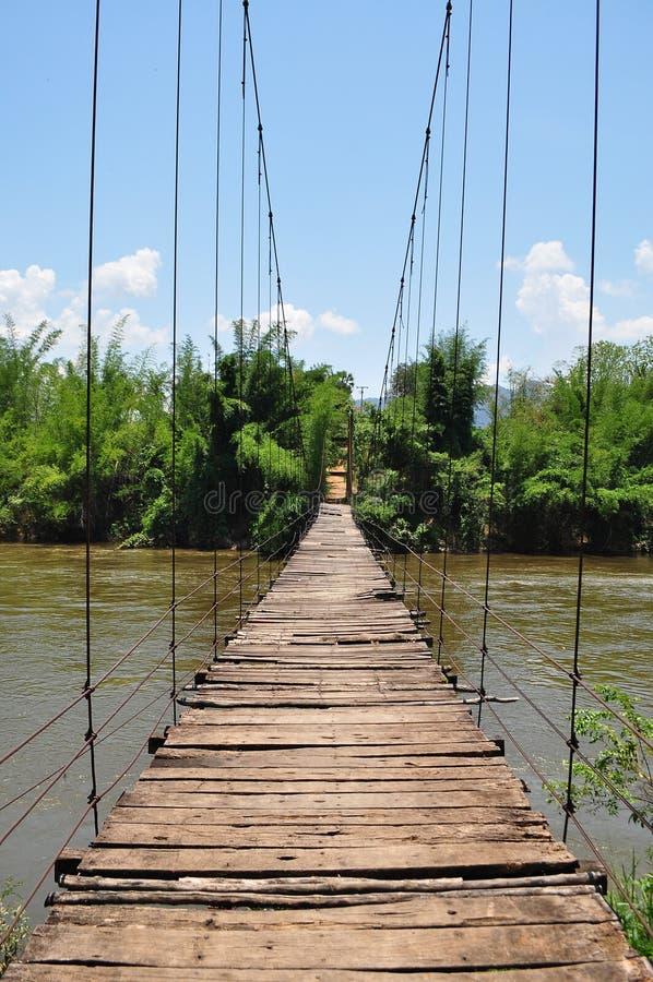 Ponte de madeira suspendida sobre um rio que conduz a uma selva em Tailândia foto de stock