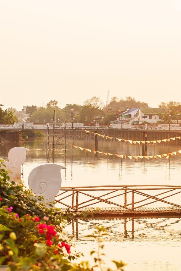 Ponte de madeira velha com a ponte embandeirada e concreta sobre Wang River, Tailândia imagens de stock royalty free