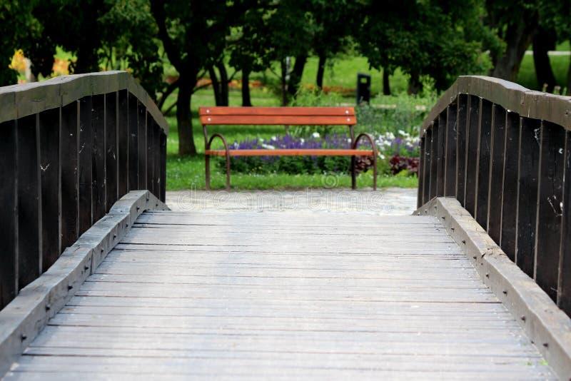 Ponte de madeira velha romântica retro do vintage que conduz para o banco de parque público de madeira com o apoio do metal cerca foto de stock