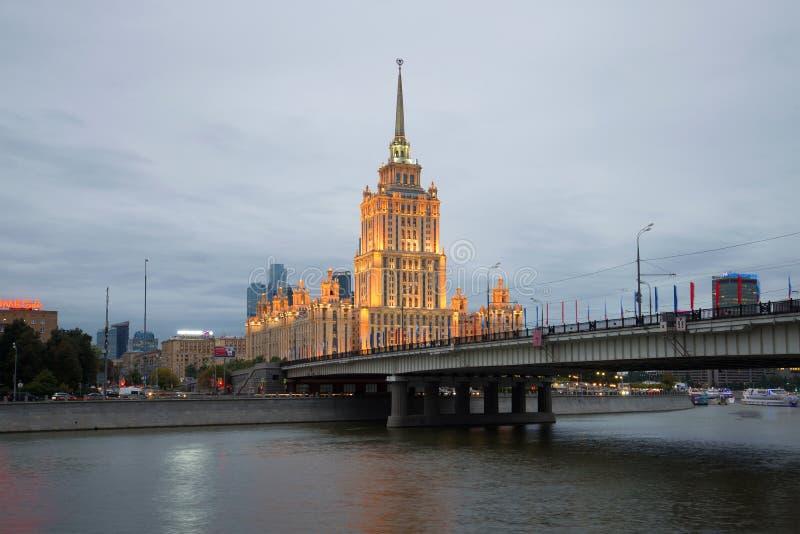 A ponte de Novoarbatsky e o hotel real de Radisson do ` de Ucrânia do ` do hotel na iluminação da noite moscow foto de stock