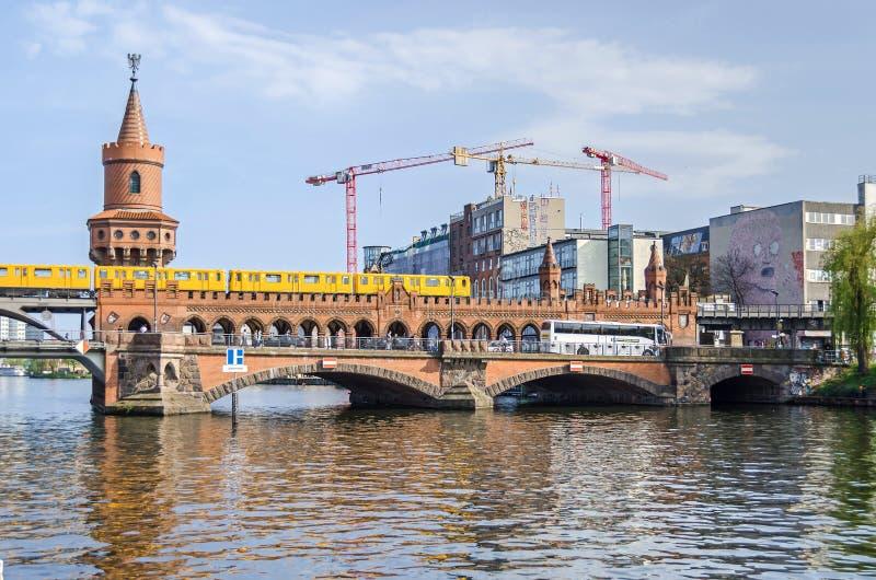 Ponte de Oberbaum com um trem de U-Bahn que cruza a e o lote de construção novo com os guindastes em Berlim imagens de stock royalty free
