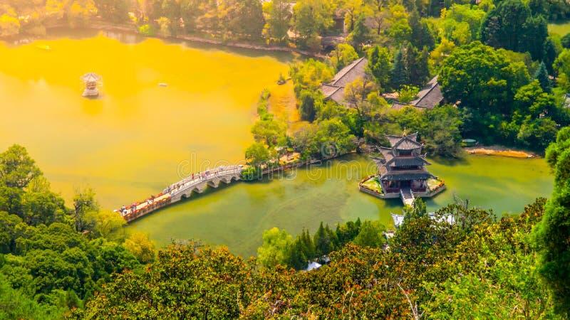 Ponte de Suocui sobre Dragon Pool preto no pavilhão do abraço da lua em Jade Spring Park, Lijiang, China Silhueta do homem de neg imagens de stock