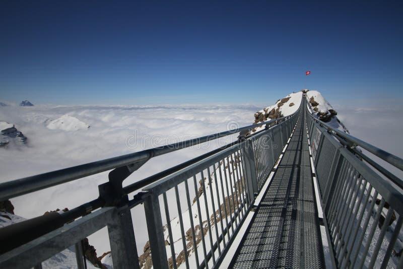 Ponte de suspensão de aço entre o fundo claro azul médio do céu do pico de montanha do gelo e nebuloso branco na estação do inver fotografia de stock