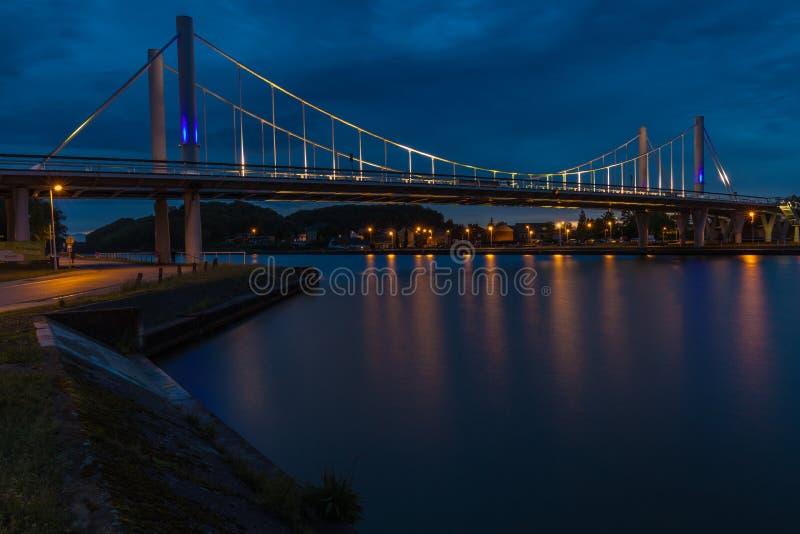 Ponte de suspensão em Kanne, Bélgica contra um céu de nivelamento dramático durante o crepúsculo fotografia de stock royalty free