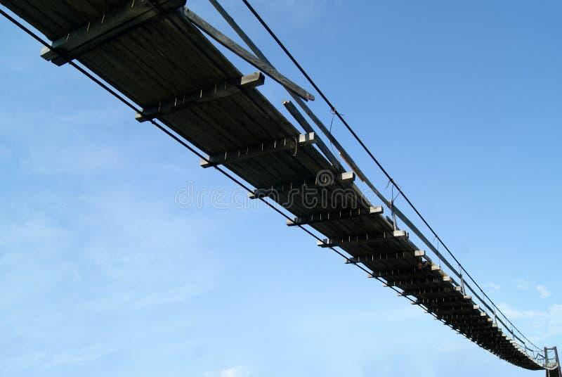Ponte de suspensão de madeira velha no fundo do céu fotografia de stock royalty free