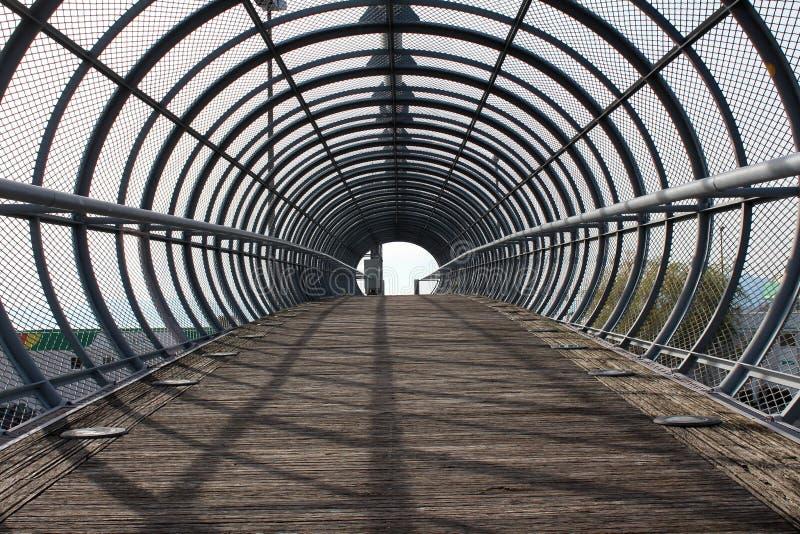 Ponte del tunnel del metallo con il passaggio pedonale di legno fotografia stock libera da diritti