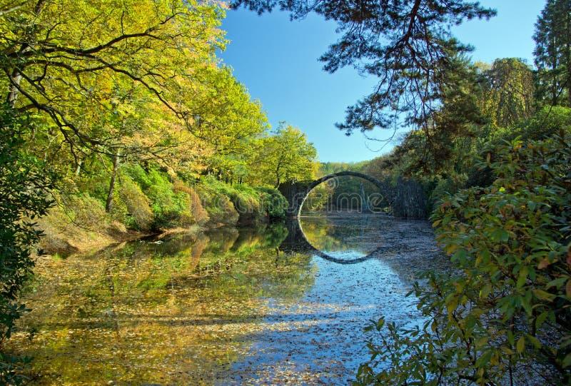 Ponte dell'arco in Kromlau, Sassonia, Germania Autunno in parco fotografia stock libera da diritti