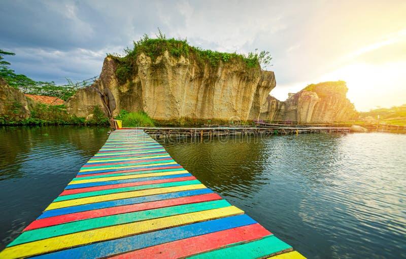 Ponte dell'arcobaleno che attraversa il lago blu pacifico in mezzo di Rocky Cliff To The Sunrise nella mattina fotografie stock libere da diritti