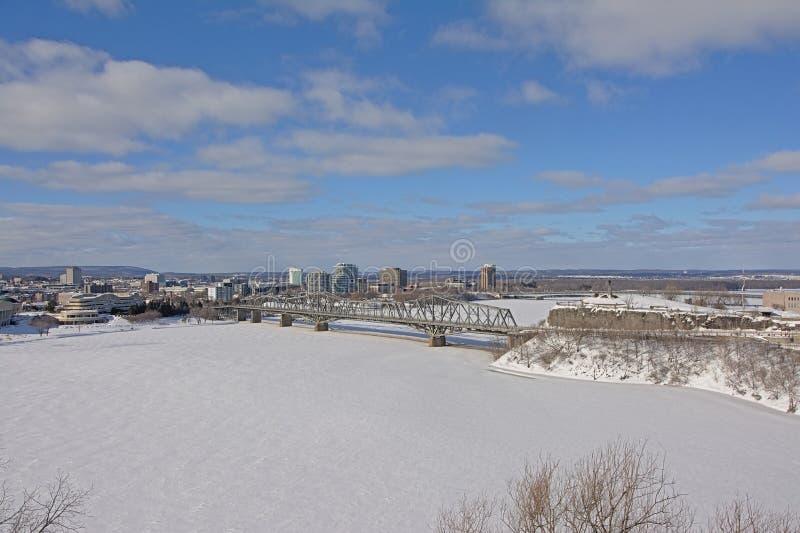Ponte di Alexandra Interprovincial sopra il fiume congelato di Ottawa il giorno di inverno con neve fotografia stock libera da diritti