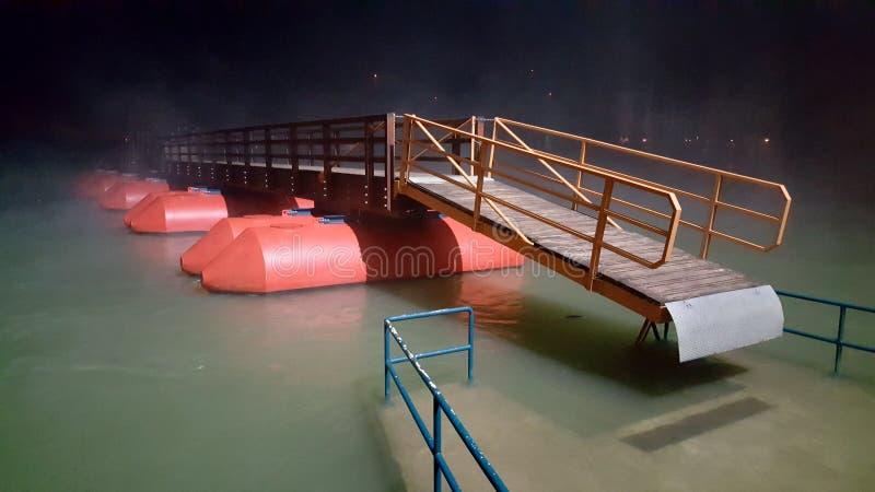 Ponte di barche di galleggiamento di legno circondato con nebbia alla notte durante l'inondazione immagini stock libere da diritti