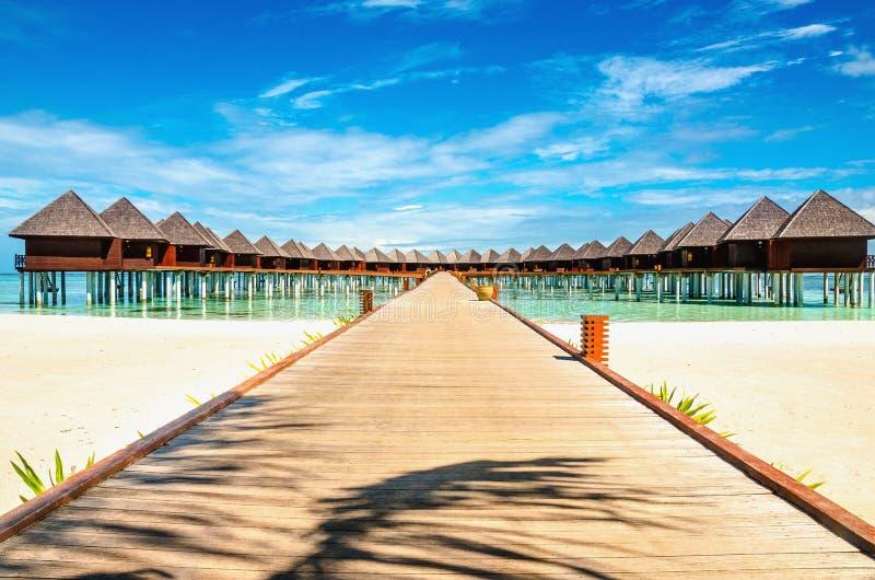 Ponte di legno che conduce ad un bungalow esotico sui precedenti di acqua azzurrata, Maldive fotografia stock libera da diritti