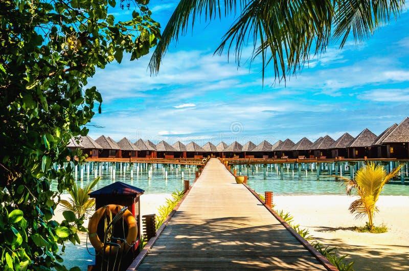 Ponte di legno che conduce ad un bungalow esotico sui precedenti di acqua azzurrata, Maldive fotografie stock libere da diritti